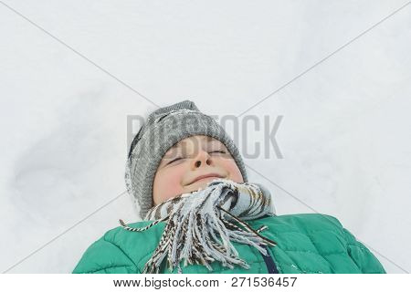 Boy In A A Hat, Scarf And A Green Jacket Is Lying On His Back In The Snow With Eyes Closed. Portrait
