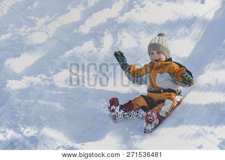 Boy In Hat And Orange Jumpsuit Slides Off Snow Slide On Back. Portrait. Close-up. Winter Day