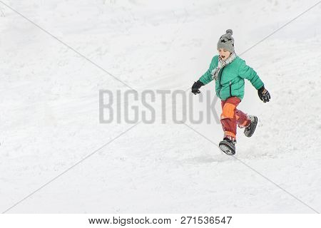 Boy In The Green Jacket And Red Pants Runs Through The Snow. Winter Day.