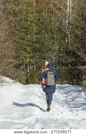 Mother With Son In Arms And Backpacker Walking Along Snow-covered Road Against The Background Of Con