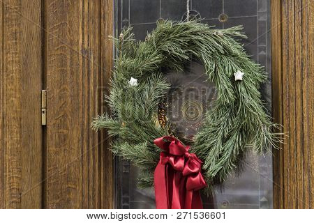 Christmas Wreath With A Red Bow Hanging On A Wooden Door.