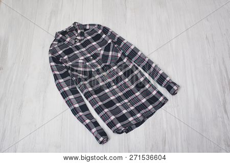 Fashionable Concept. Checkered Shirt On A Wooden Background. Female Wardrobe