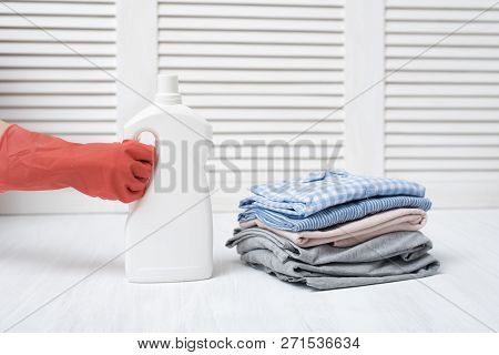 Stack Of Folded Clothes And Detergent Bottle In Female Hand. Housework