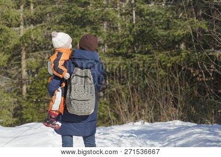 Mother With Son In Arms And Backpack Stands Against The Background Of Coniferous Forest And Snow-cov
