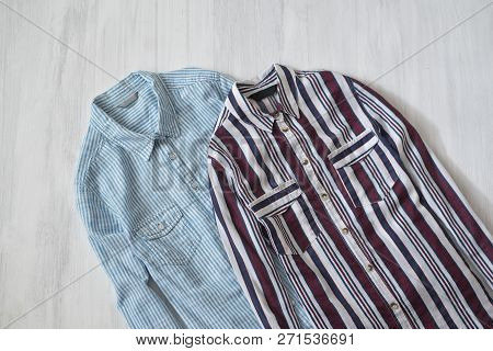 Two Striped Shirts On Wooden Background. Fashionable Concept