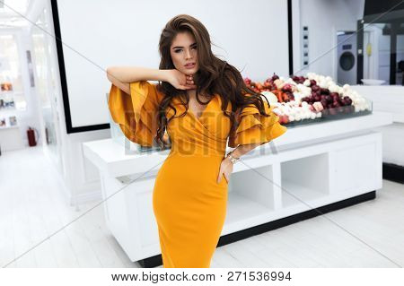 Gorgeous woman with volume brunette hairstyle, wearing evening cocktail yellow dress with sleeves and decollete. Party makeup on the face, big lips, white teeth. Standing near the vegetable counter. poster
