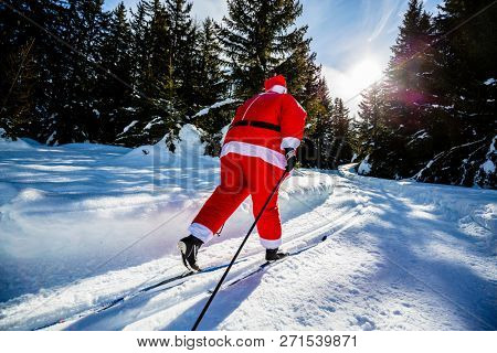 Fat Santa Claus with Christmas suits with classic  nordic ski in snowy winter mountain ski resort landscape in sunny day, New Year's or xmas is coming.