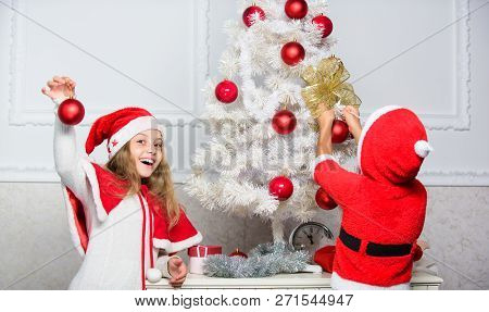 Kids in santa hats decorating christmas tree. Family tradition concept. Children decorating christmas tree together. Boy and girl decorating tree. Siblings busy decorating. Cherished holiday activity poster