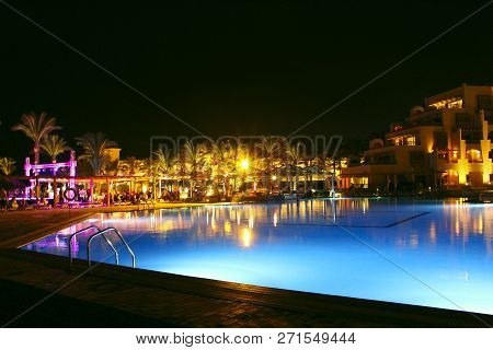 Hurghada / Egypt. 30 July 2018: Pool And Evening Hotel On Vacation. People Relax By Evening Near Poo