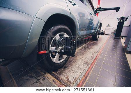 Mechanic Tuning Aligner For Wheel Alignment In Garage Closeup. Professional Car Maintenance In Moder