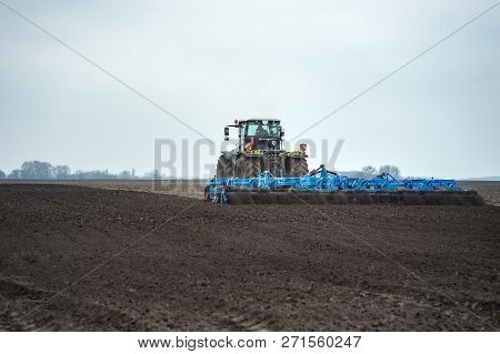 Preparing Land And Fertilizing. Seedbed Cultivator In Farmlands. Tractor Plows A Field.  Agricultura