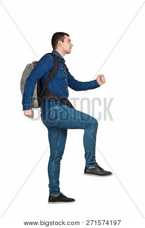 Side View Full Length Portrait Of Confident Young Man Carrying A Backpack And Climbing An Imaginary