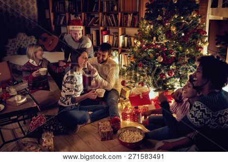 Group of happy friends sitting next to a Christmas tree, and having fun.