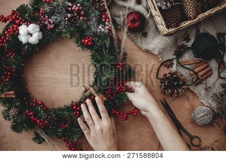 Rustic Christmas Wreath Flat Lay. Hands Holding Fir Branches, Red Berries And Pine Cones,thread, Sci