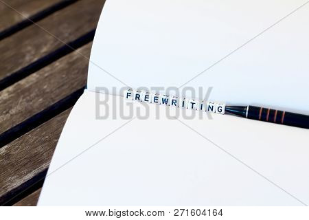 Notebook And Pencil On Table With White Cube Letters 'free Writing'. Dark Brown Wooden Background. C