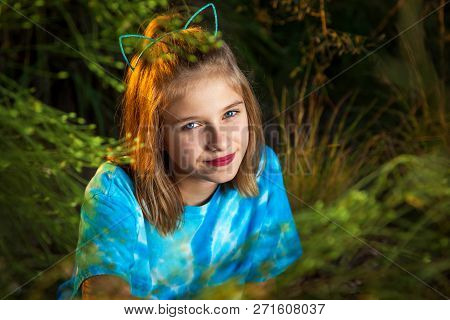 A Sassy Looking Girl Wearing A Head Band With Cat Ears Looks At The Camera With A Tilted Head And A