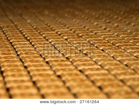 Close-up of lots of crackers moving on a confectionery fabric conveyer
