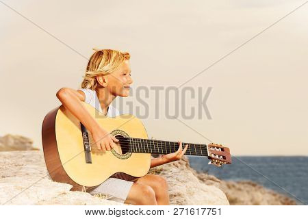 Happy Boy Teenager Playing Guitar At The Seaside