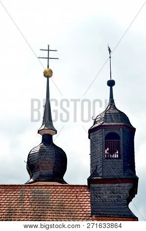 Two Towers Are On The End Of A Roof. One Has A Golden Orb And Double Cross. The Other Is Bell Tower.