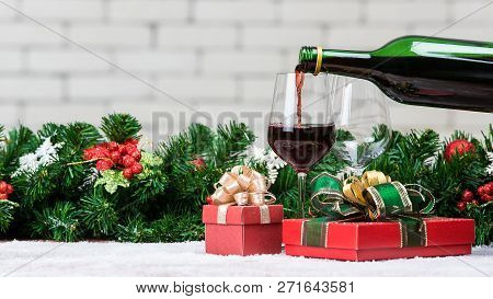 Red Wine Is Pouring From Bottle In To Glass Decorating With Red Gift Boxes And Christamas Ornaments.