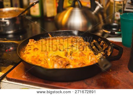 Fresh Enchiladas Or Burritos Covered In Pepper Sauce And Cheese In A Cast Iron Pan. Home Kitchen Set