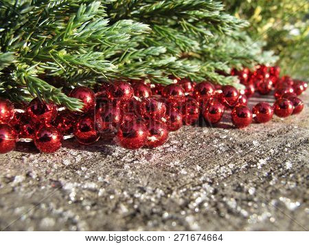 Red Beads And Conifer Branches On A Background Of Rustic Wood With Snow In Sunny Day. Space To Copy,