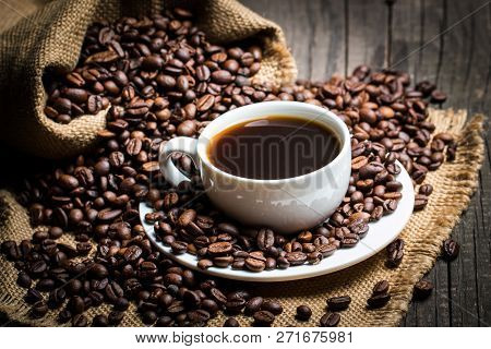 Coffee Cup And Beans On A Rustic Background. Coffee Espresso And A Piece Of Cake With A Curl. Cup Of