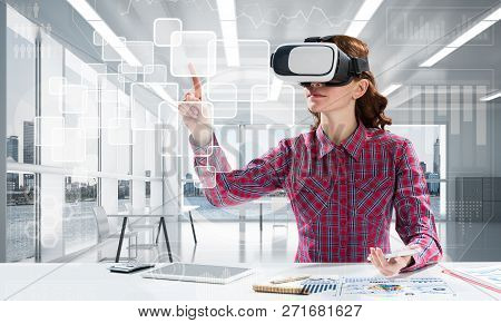 Young Woman In Checkered Shirt Using Vr Headset With Digital Media Interface While Sitting Inside Br