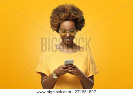 Young African American Woman In Yellow T-shirt And Trendy Eyeglasses Looking At Screen Of Phone And