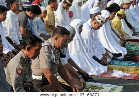 JAKARTA, INDONESIA - SEPTEMBER 20: Police officers pray with other Muslims outside a mosque in Jakarta on Hari Raya, the end of a month of fasting called Ramadan September 20, 2009 in Jakarta.
