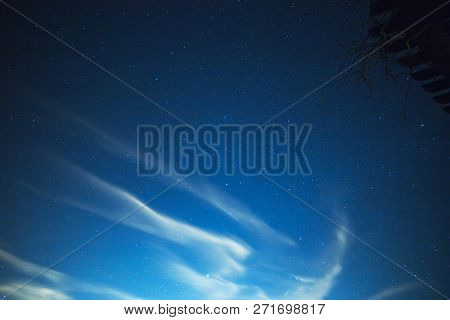 Soft Clouds Drifting In A Night Sky With Stars Above.
