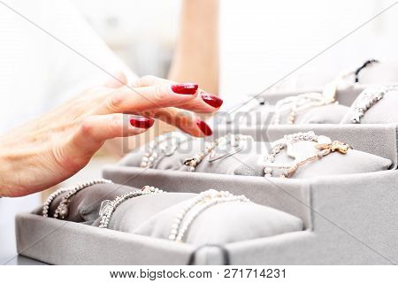 Jewelry And Accessories. A Woman Is Watching Jewelry In A Jewelry Salon