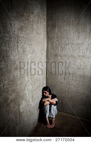 Abused woman in the corner of a stairway comforting herself