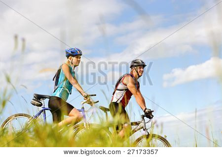 Happy couple riding bicycles outside, healthy lifestyle fun concept