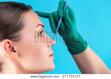 Cosmetic Surgeon Examining Female Client In Office. Doctor Checking Womans Face, The Nose Before Pla