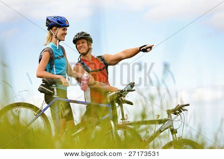 Happy mountainbike couple outdoors have fun together on a summer afternoon