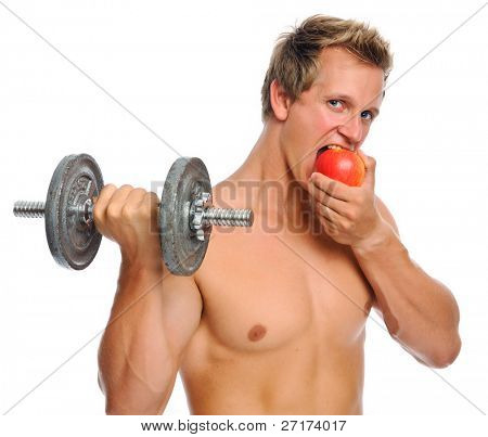 Handsome muscular man eats an apple while doing bicep curls