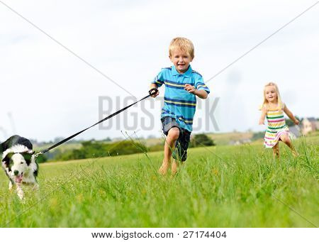 Young boy runs in a green field with his new pet with his sister following behind
