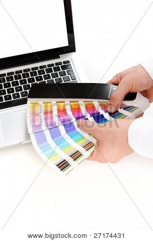 Tools of the trade of a graphic designer; a laptop computer and a spectrum of color swatches