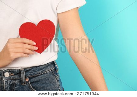 Woman Holding Heart Near Hand With Adhesive Plasters Against Color Background, Closeup. Blood Donati