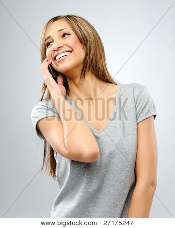 Happy smiling brunette looks sideways while on the phone