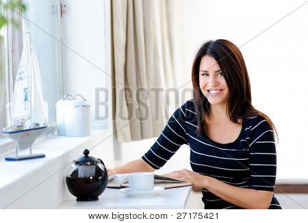 Pretty woman relaxes at home by the window with her tea and book