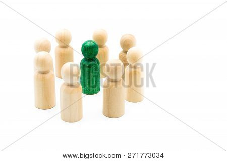 Green Figure Standing Out From The Crowd Inside Circle Of Wooden Figures