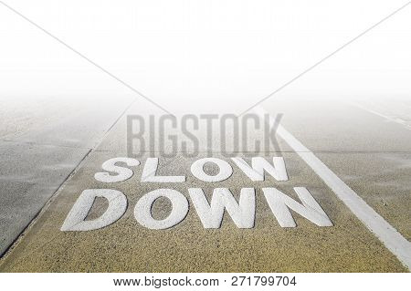 Big Slow Down Sign On A Footpath Disappearing In White Fog
