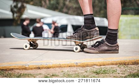 Foot Of Unknown Man On Top Of Skateboard Ready To Roll