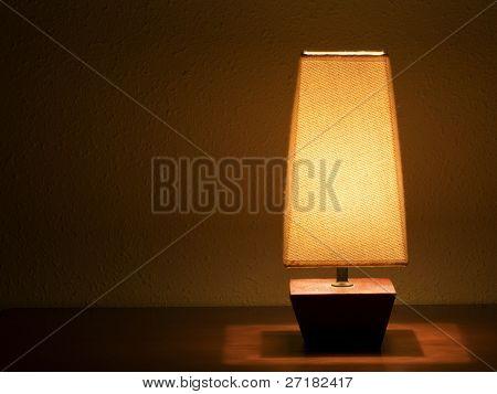 Lit bedside lamp over nightstand
