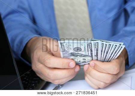 Man In Shirt And Tie Holding Us Dollars In Hands, Close-up. Clerk, Official Or Businessman Takes The