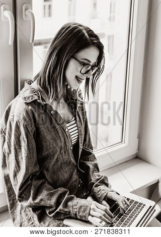 Portrait Of Young Self-employed Woman With Laptop Sitting Near Window At Home. . Image In Black And