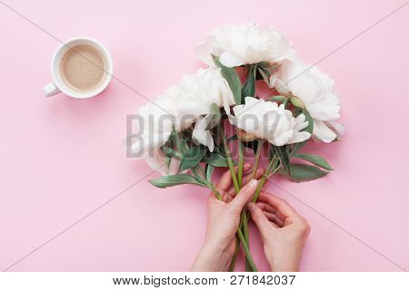 Woman Hands With Beautiful White Peony Flowers And Cup Of Coffee On Pink Pastel Table Top View. Cozy