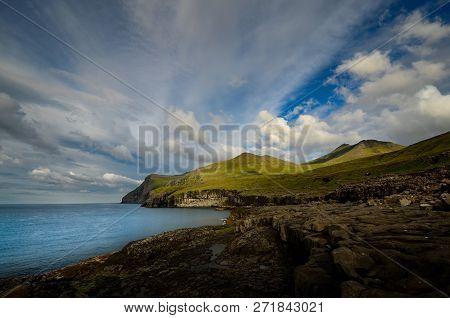 Island And Mountain Range Beneath Cloudy Sky